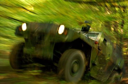 storming: Military off-road vehicle storming through forest, long exposure time was used to create dramatic motion blur effect.