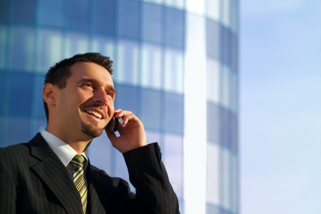 Attractive young businessman using a cell phone, smiling. Taken in front of a modern office building on a beautiful sunny day. Landscape/horizontal orientation with copy space on the right.