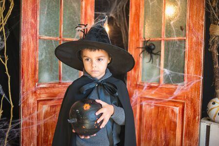 Caucasian boy in carnival wizard costume with black painted pumpkin on Haloween decor background. Halloween, carnival, masquerade, childhood, fairytale theme. 写真素材