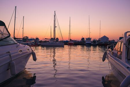 Yachts and reflections against backdrop of beautiful sunset.