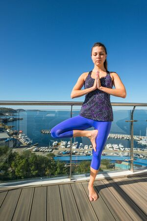Active young girl in a tree pose on an open terrace on the background of the sea. The concept of a healthy lifestyle. Yoga classes.