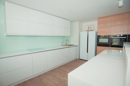 Modern white kitchen with wooden panels. toned 写真素材