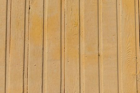 Textures of wooden boards, painted with yellow paint, vertically arranged, in places peeling off. Фото со стока