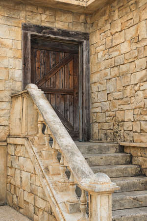 Old wooden door, staircase with handrails, stone building. Architecture, building theme.