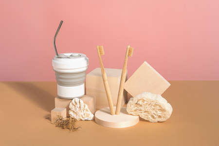 Reusable coffee cup, bamboo toothbrushes, loofah washcloth on wooden podiums, pink and beige background. Zero waste concept. Stock fotó