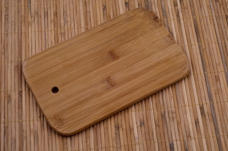Wooden Bread board on wooden bamboo background Stock Photo