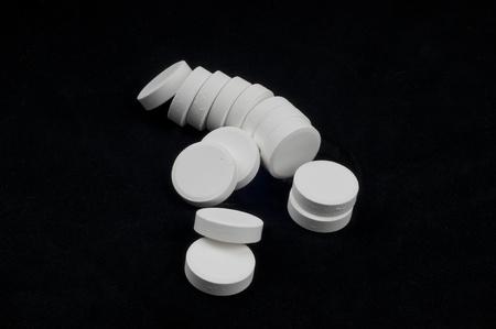 White Vitamin Tablets on black backgrounds