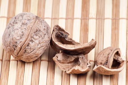 Walnut and some shells on bambo background Stock Photo
