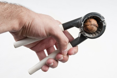 Human hand Nut Cracker pressing in the nut Stock Photo