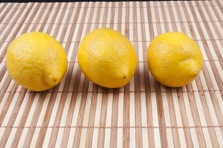 Three lemon on bamboo background Stock Photo - 13283680