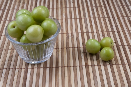 Fresh green plums in the plate and ground  on bamboo background