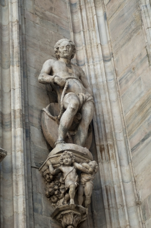 Statue of man  wall of duomo Cathedral in milano photo