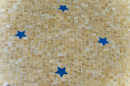 Blue stars on the yellow ground mosaic on milano italy