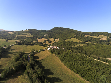 aerial shot of a little village surrounded by nature of Monti Sibillini National Park , Collevecchio, Macerata, Italy