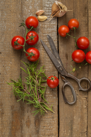 Cherry Tomatoes, Garlic & Scissors On The Wooden Background photo