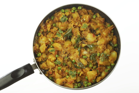 Cooked spicy potato preparation with other vegetables like onion and green peas.