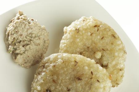 marathi: Fast food deep fried sago sabudana vada with chutney on white background.