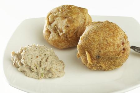 marathi: Fast food deep fried batata potato vada with chutney on white background.