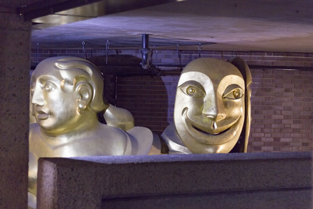 tragedy: London, England - May 19, 2016: The Barbican Muse is a sculpture by Matthew Spender and represents a woman holding tragedy and comedy masks in London, England.