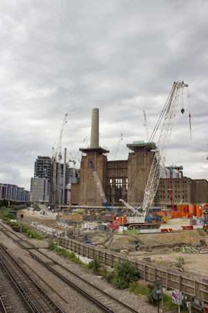 deconstruction: London, England - May 22, 2016: Construction cranes over the Battersea power station currently being rebuilt, and transformed into luxury housing, shops and entertainment in London, England.