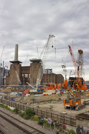 battersea: London, England - May 22, 2016: Construction cranes over the Battersea power station currently being rebuilt, and transformed into luxury housing, shops and entertainment in London, England.