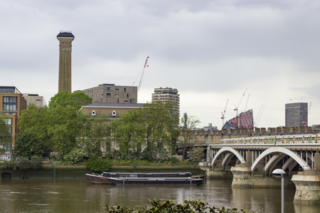 battersea: London, England - May 22, 2016: Construction of buildings with cranes behind River Thames and opposite Battersea Power Station in London, England.