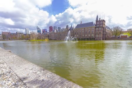 ministry: Parliament buildings of the Binnenhof and Hofvijver pond in front of the skyline of The Hague, The Netherlands.
