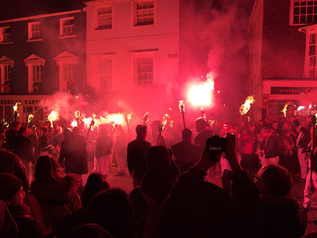 Lewes, England - 5 November 2016: Dark and crowded streets of Lewes are covered in smoke due to the explosions and fire parade of the yearly celebration of the Bonfire night festivities. Editorial