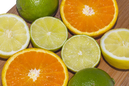 bitter orange: A selection of chopped oranges, lemons and limes on a wooden board on white background. Stock Photo