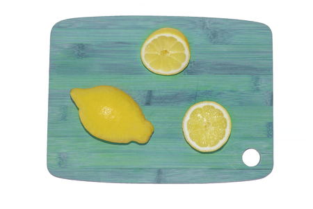 Sliced lemon on a wooden chopping board on white background