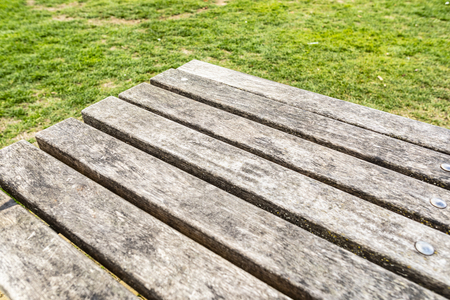 Close up of an outdoor vintage wooden table with grass background. Perfect for product placement.
