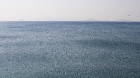 Summer view of quiet waves on the sea horizon line on a sunny day.