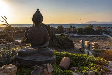 Sunset over the representation of the sitting protection Buddha hand gesture and posture - with right hand raised, facing outward, left hand resting in lap, and seated with one leg resting on top of the other (Single Lotus) - with sea and beach as a background.
