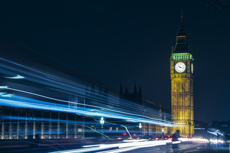 The iconic British Elizabeth Tower with Big Ben at the top and its clock face, near the houses of parliament in the city of Westminster, London in England, Great Britain seen at night with traffic light trails passing in front. Long exposure.