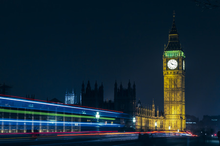 The iconic British Elizabeth Tower with Big Ben at the top and its clock face, near the houses of parliament in the city of Westminster, London in England, Great Britain seen at night with traffic light trails passing in front. Long exposure. 版權商用圖片 - 112484017