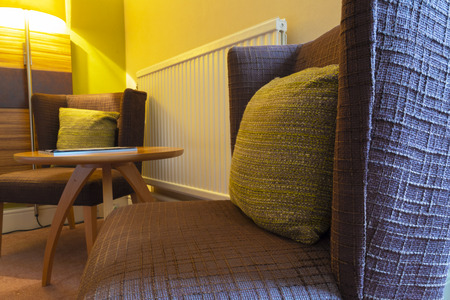 Shot of a cosy lounge area with two armchairs, a coffee table and a bright lamp, with floor covered with carpet.