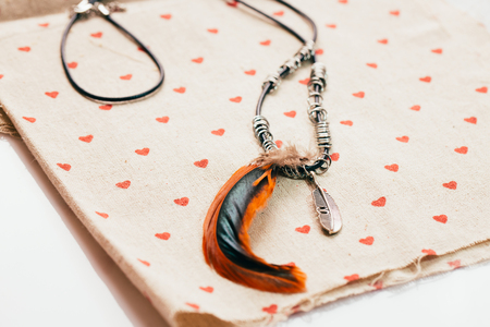 pendant with feathers on fabric background hearts. Stock Photo