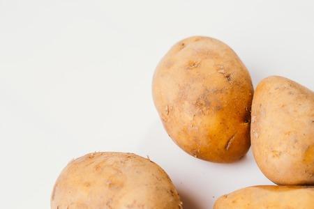Fresh raw potatoes on a white background.