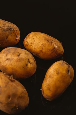Fresh raw potatoes on a black background.