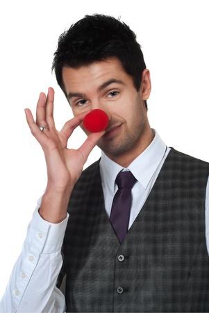 Young man magician making clown nose photo