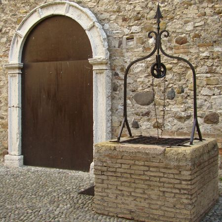 wishing: beautiful ancient well in italian courtyard, Sirmione castle                                Stock Photo