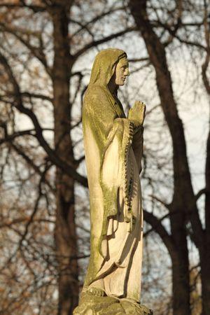 religious habit: ancient figure of praying monk on historic cemetery, Poland