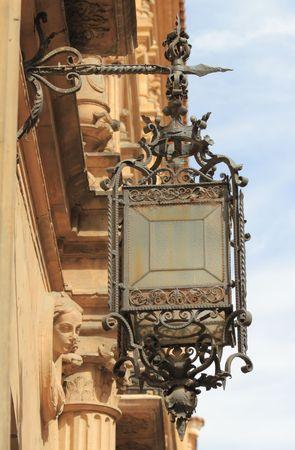 antique lamp on historic facade, Spain photo