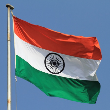 flag of India with flag pole waving in the wind over blue sky Stock Photo