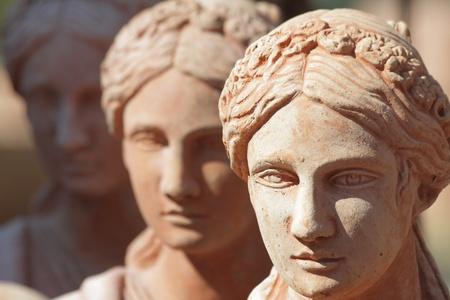 three women: traditional tuscan earthenware garden sculptures closeup