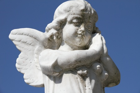 sculpture of little praying angel - isolated on sky  photo