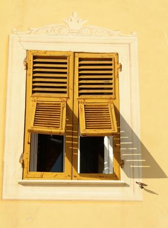 stucco facade: socchiusa persiane gialli nella finestra italiano, Liguria