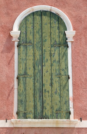 arc window with green wooden shutter in Venice photo