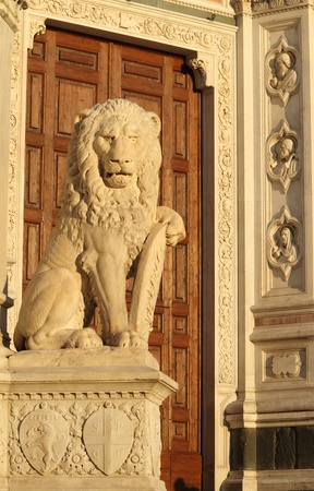 detail with marble lion and wooden door on Piazza Santa Croce in Florence at sunset, Italy