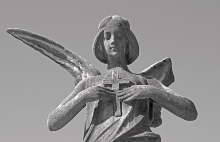 monumental cemetery: antique sculpture of the angel holding a cross on chest, Italy